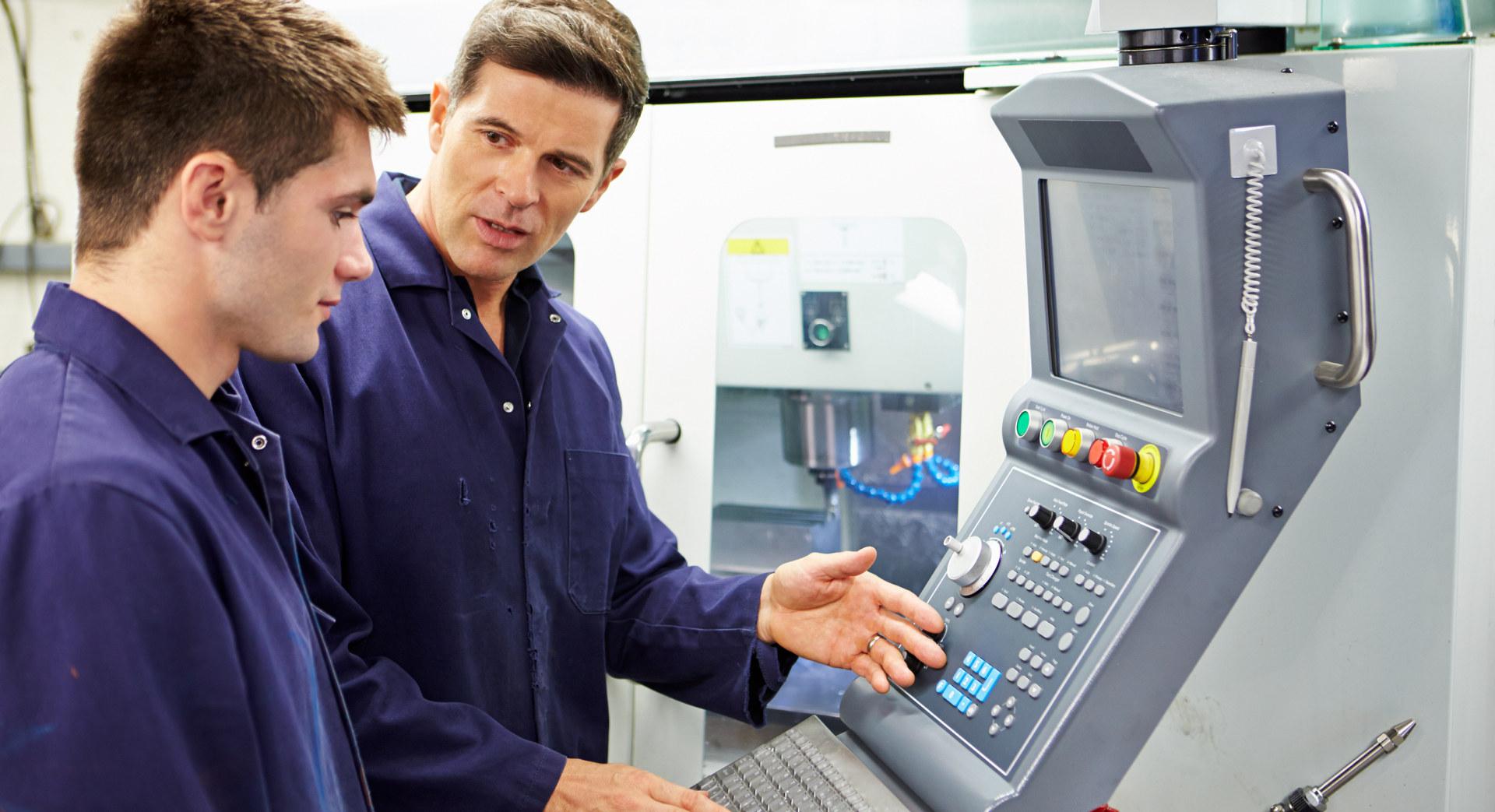 To personer ser på en maskin