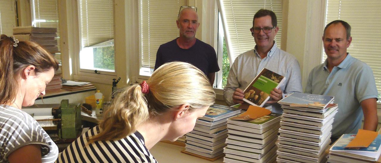 Tre menn som står bak en stabel med bøker