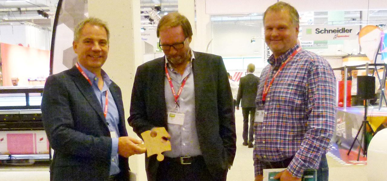 Tre menn som viser frem et produkt på et trykkeri