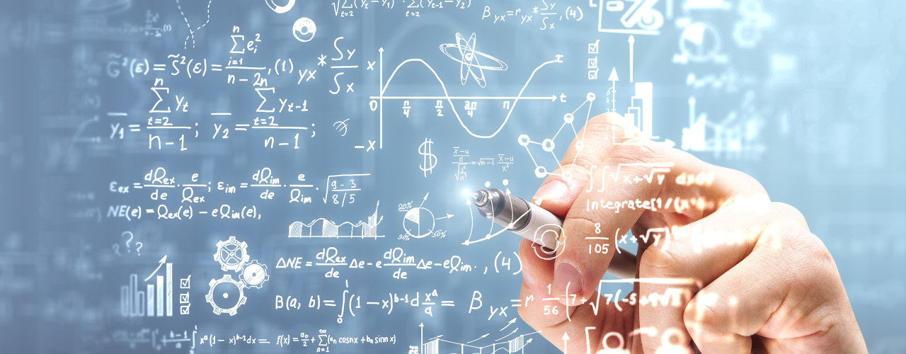 En hånd som holder i en penn og skriver på en tavle