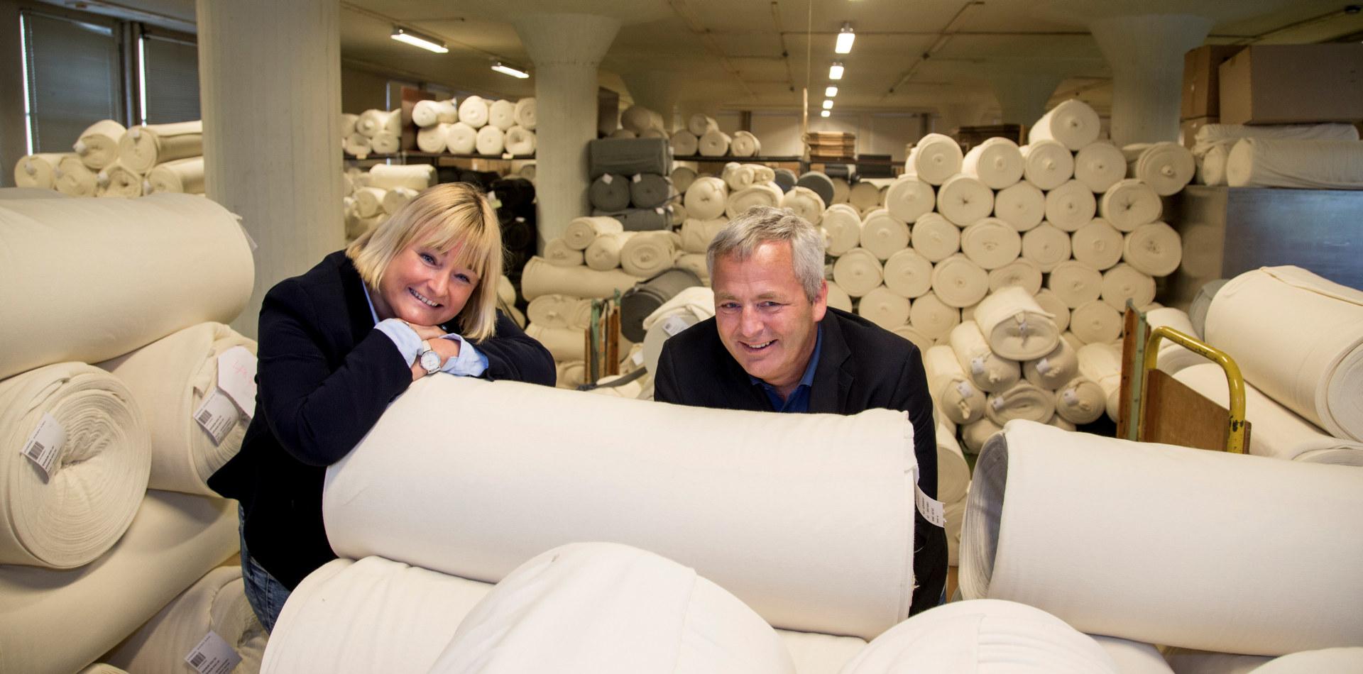 Konsernsjef i Janus-konsernet, Janne Vangen Solheim og administrerende direktør for Janusfabrikken, Arne Fonneland, på lageret for ferdigstrikkete ruller med ullstoff.