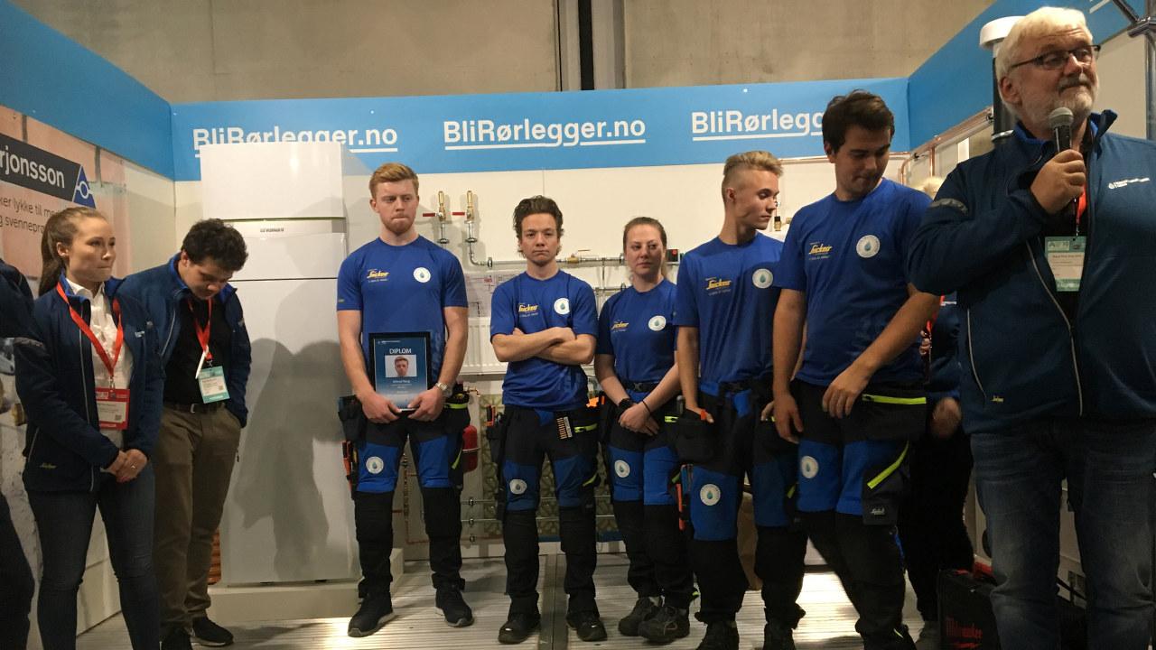 Erlend Haug midt i bildet med diplom og de andre finalistene ved siden av seg. Hoveddommer Helge Andersen til høyre med mikrofon.
