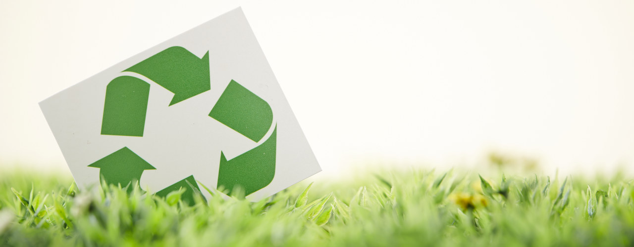 Gjenvinning illustrasjon, resirkuleringslogo på gress