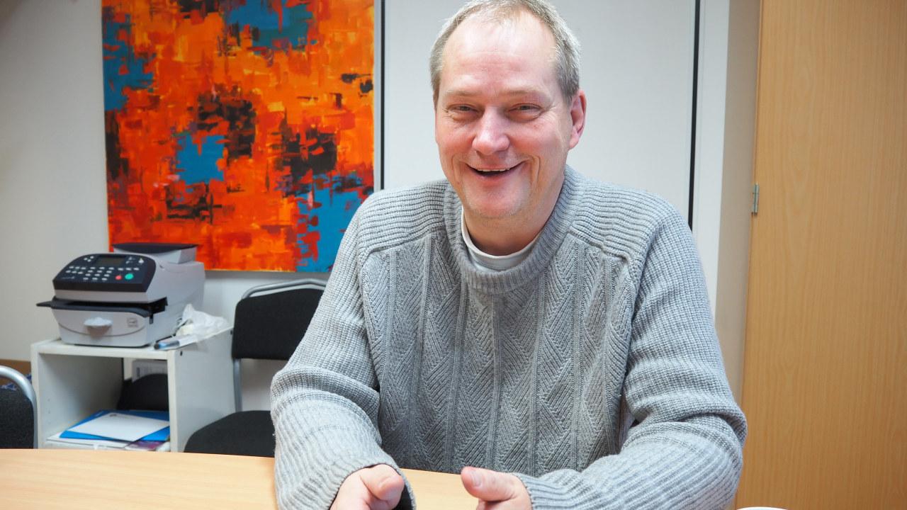 Mann som sitter ved en kontorpult og smiler