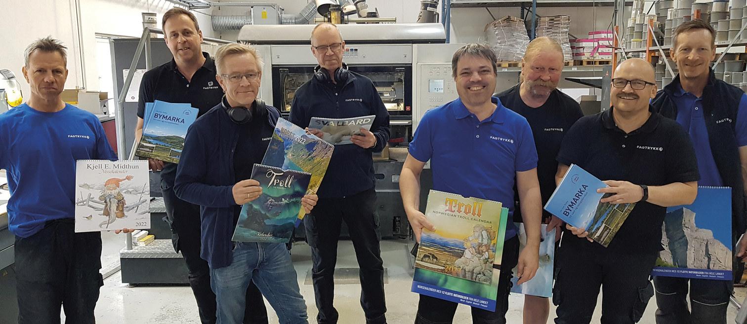En gruppe menn i et trykkeri som viser eksempler på trykksaker