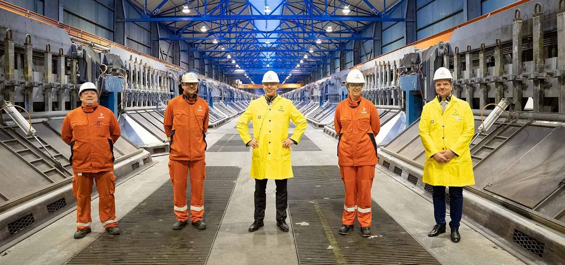 Fem mennesker i fabrikkhall