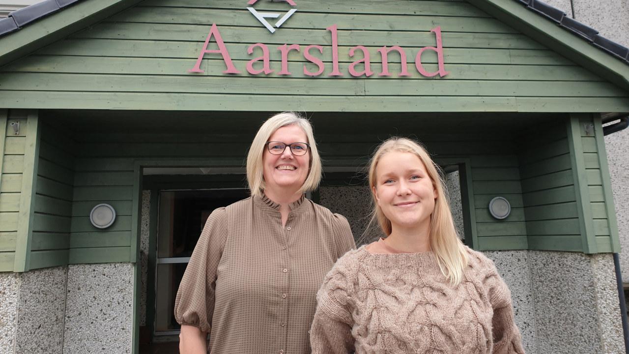 To damer forran inngangsparti til Aarsland Møbelfabrikk